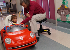 A new innovative program called GoBabyGo is introduced. A young girl is pictured in a ride on car learning mobility supporting by her therapist.