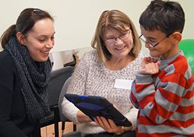 A mother is pictured looking on as her son's therapist is demonstrating how to make a sentence using an iPad used to provide Augmentative Communication through technology.